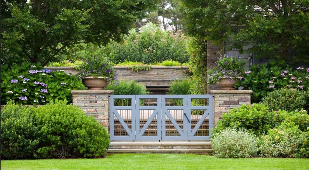 Wild gardens framing a grand garden gate. NelsonByrdWoltz.com