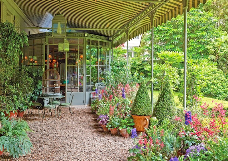 A canvas roof makes a cozy, secluded spot in a Parisian garden. ArchitecturalDigest.com.