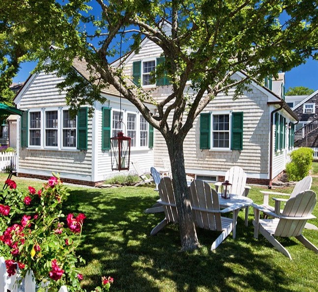 Even this small tree beside a Cape Cod cottage makes an inviting destination. Atlantic Bay Sotheby's International Realty, on ArchitecturalDigest.com.